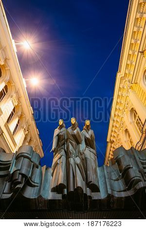 Vilnius, Lithuania - July 8, 2016: Close The Black Sculpture Of Three Muses On Facade Of Lithuanian National Drama Theatre Building, Main Entrance, Blue Evening Sky Background.