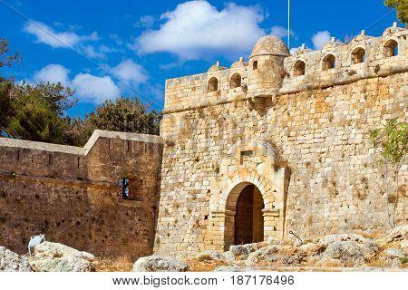 Main (Eastern) Gate of Fortezza Castle - Venetian fortress on hill Paleokastro in resort Rethymno. Greek architecture on coast of Kolpos Almirou. Crete Greece