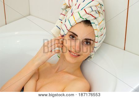 a wonderful young girl with towel on the hair lies in the bathtub and a smiling close-up
