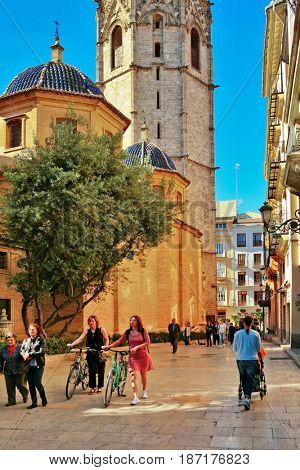 VALENCIA, SPAIN - APRIL 23, 2016: Residents and tourists walk along street near tower Miguelete (Micalet) is known as bell tower of the Cathedral of Valencia. This is a Gothic tower 51 meters high