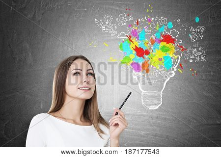 Inspired Woman With Pen And Colorful Light Bulb