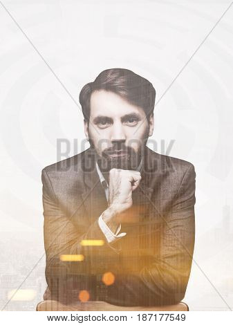 Portrait of a serious bearded businessman wearing a brown suit and leaning on a chair. He is looking at the viewer and portraying confidence. Toned image