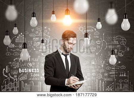 Portrait of a bearded businessman in a black writing down his business idea in a room with blackboard and many light bulbs on wires