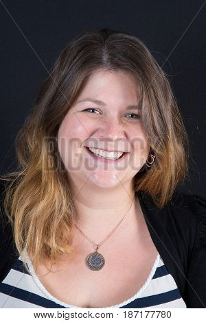 a chubby woman smiling in black background