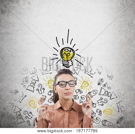 Portrait of a businesswoman in glasses standing with crossed fingers near a concrete wall with a light bulb sketch and black and yellow business icons