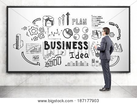 Side view of a young businessman holding a paper cup of coffee and looking at a whiteboard with business idea icons