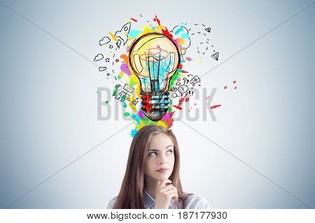 Pensive young woman with long hair is standing near a gray wall with a colorful light bulb and business sketches buzzing around