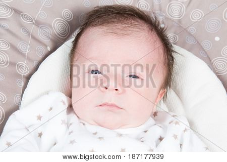 a caucasian newborn baby looking in bed