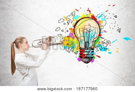 Side view of a blond businesswoman playing on a trumpet near a concrete wall with a colorful light bulb and business ideas buzzing around