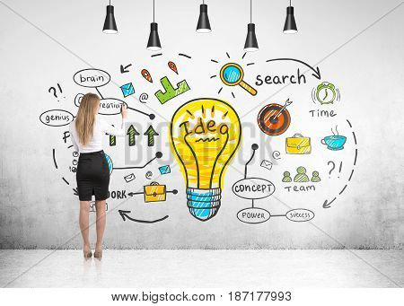 Rear view of a blond businesswoman drawing a bright business idea sketch on a concrete wall of a room with many ceiling lamps