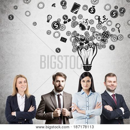 Successful business team members are standing near a concrete wall with a light bulb with smaller icons drawn above them