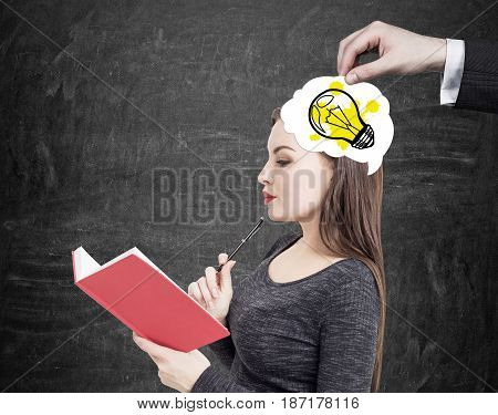 Close up of a businessman s hand putting an idea into a head of a woman in gray dress reading a red book