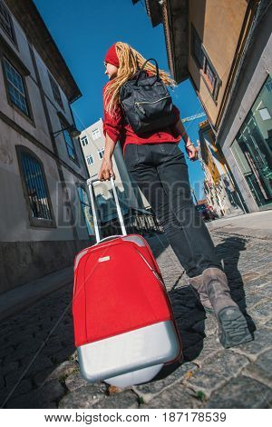 Traveler girl walking in city with red suitcase.