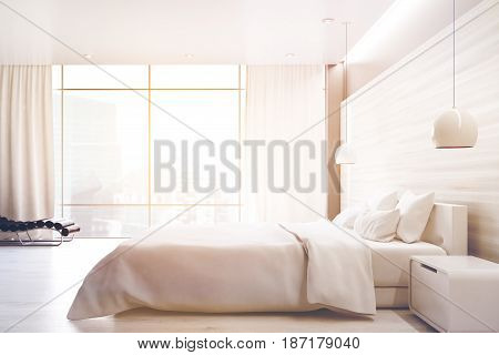 Side view of a white wall bedroom interior with a double bed a bedside table an armchair and a large window. 3d rendering toned image