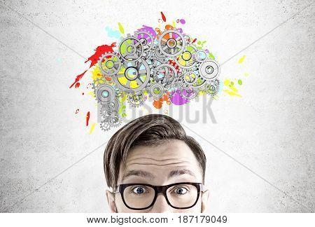 Close up of a head of a man wearing glasses and standing near a concrete wall with a colored brain shape and gears on top of it.