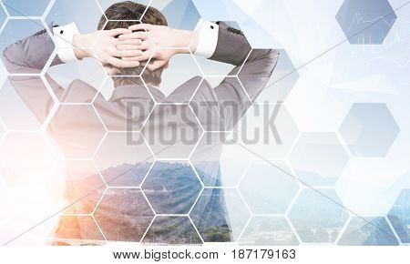 Rear view of a businessman standing with his arms behind the head and looking at green heels and graphs. Hexagons in the foreground. Mock up toned image double exposure