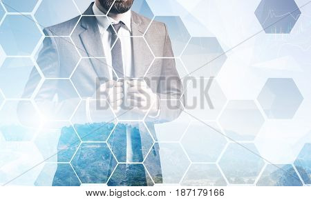Close up of an unrecognisable bearded businessman standing against green heels and graphs. Hexagons in the foreground. Mock up toned image double exposure