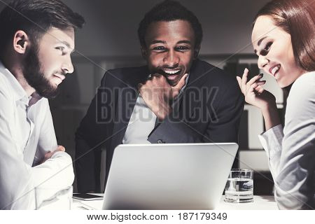 Three business partners are sitting at a table with a laptop and brainstorming trying to find the best strategy. Toned image