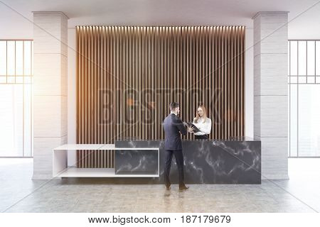 Businessman is talking to a receptionist at a black marble reception counter of an original construction standing near a wall with wooden vertical blinds. 3d rendering toned image