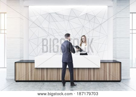 Businessman is talking to a receptionist at a wooden and white reception counter of an original construction standing near a white wall with a geometric pattern on it. 3d rendering