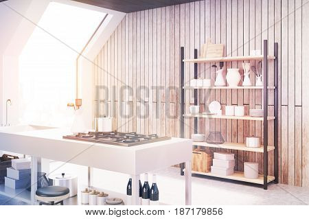 Side view of an interior of an attic kitchen with wooden walls a cooker a sink and a cupboard with dishes and cutting boards. 3d rendering mock up toned image
