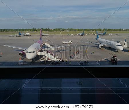 KIEV - UKRAINE - MAY 2017: View from the window of the terminal to the runway. On the runway are aircraft. Passengers climb the ladder. Technical Service prepares aircraft for flight