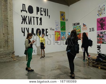 KIEV, UKRAINE - MAY 2017:  People visit the art and book exhibition in Arsenal museum in Kiev. Girl make a photos by mobile. Another girl drink a coffee