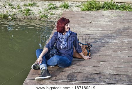 A young woman enjoying a beautiful summer day on the river wooden pontoon.