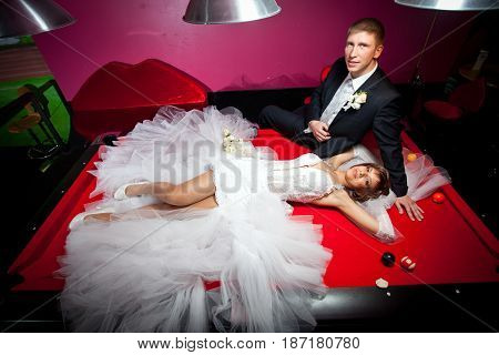 Beautiful Girl In A White Wedding Dress Lying On A Red Table To Play American Pool.