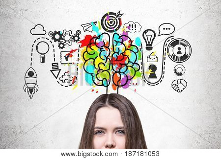 Close up of a young woman s head with brown hair. She is standing near a concrete wall with a start up sketch and a colorful brain icon