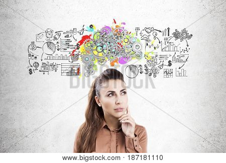 Portrait of a pensive businesswoman wearing a brown blouse and standing near a concrete wall with a business scheme and a brain with gears