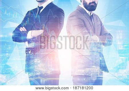 Close up of two unrecognisable businessmen standing with crossed arms against a cityscape with graphs in the background. Toned image double exposure