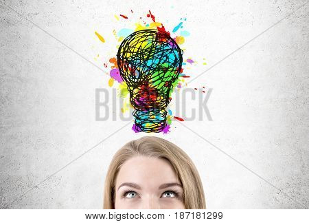 Close up of blond businesswoman s head. She is looking at a large colorful light bulb sketch drawn on a concrete wall.