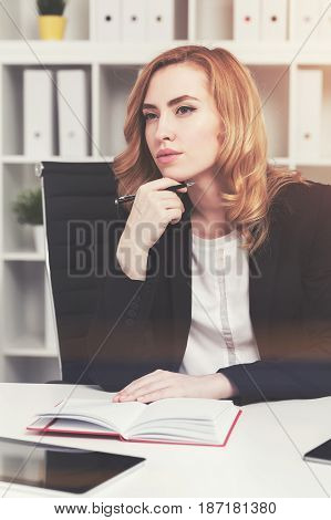 Portrait of a pensive red haired businesswoman sitting at her table with a notebook and a pen. Toned image