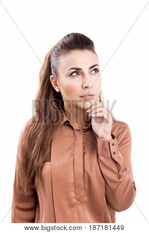 Isolated portrait of a young pensive businesswoman with long hair wearing a brown blouse and standing with a finger near her chin