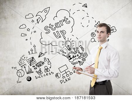 Portrait of a young businessman with a clipboard and a pencil standing near a concrete wall with a start up sketch