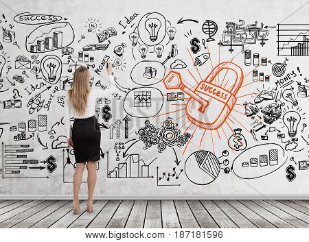 Rear view of a young blond businesswoman drawing a business scheme a lock and a key on a concrete wall.