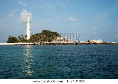 White lighthouse standing on island beach with rocks in Belitung at daytime with no people around.