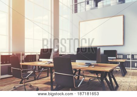 Close up of an open office interior with panoramic windows rows of wooden computer desks and a whiteboard hanging on a gray wall. 3d rendering mock up toned image