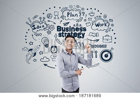 Portrait of a cheerful Asian businessman pointing upwards and standing near a gray wall with a business strategy sketch on it.