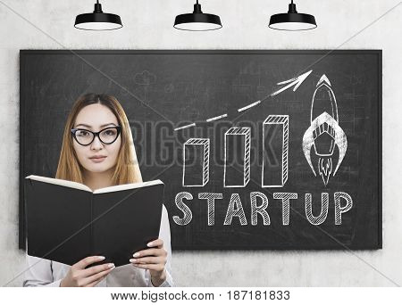 Portrait of an Asian woman in glasses reading a book and standing with near a blackboard with a start up graph