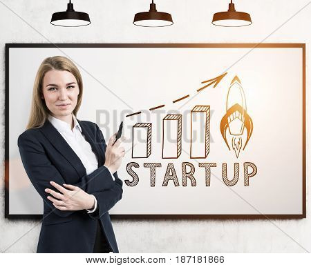 Portrait of a smiling blond businesswoman with a marker standing near a whiteboard with a start up graph on it. Toned image