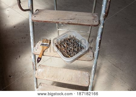 Nails and screws are in the plastic box and brush are on the wooden step of ladder