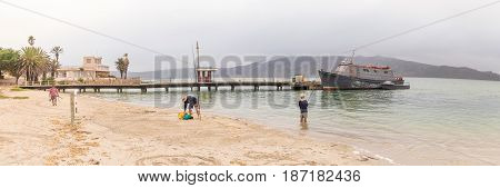 LANGEBAAN SOUTH AFRICA - MARCH 31 2017: A boat anchored at a pier and anglers at Langebaan on the Atlantic Coast of the Western Cape Province