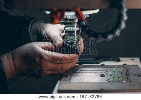 View of worker hands while he is changing drilling tool cutter in CNC milling machine during pause of treatment of aluminum blank fixed on moving table in dark settings of workshop room