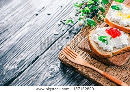 Toasts with ricotta or farmers cheese. Textured black wood background with natural golden wood tableware and apple blooming twigs. Selective focus