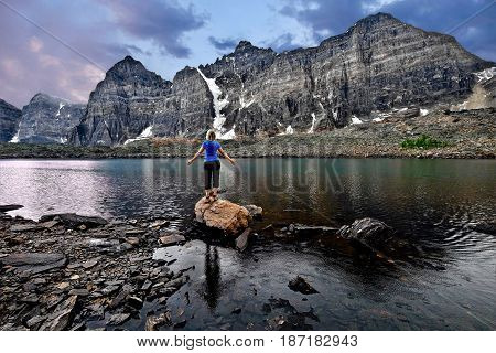Meditation by lake in Valley of Ten Peaks. Inner peace. Young woman meditating. Banff National Park. Eiffel lake. Wenkchemna Pass. Canadian Rocky Mountains. Alberta. Canada.