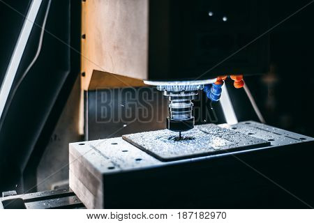 Side view of CNC milling machine manufacturing process with flying-off metalworking chips and rotating cutter which is drilling paths in aluminum raw detail with copy space for text or your logo