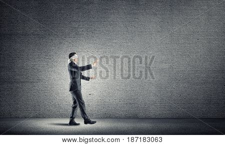 Blind businessman stepping carefully to find his way