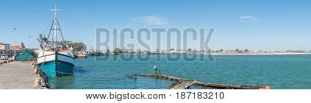 LAAIPLEK SOUTH AFRICA - APRIL 1 2017: Panorama of fishing ships and a sunken boat in the harbor at the mouth of the Berg River at Laaiplek on the Atlantic coast of South Africa